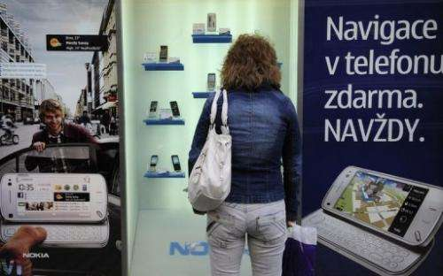 Woman looks at mobile phones on display on May 7, 2010 in Prague