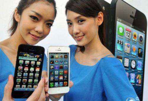 Women hold the Apple iPhone 5 during a launch at a store in Taipei on December 14, 2012