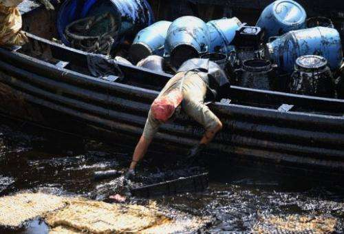 Workers collect oil from the water outside a dock in Dalian, China's northeastern Liaoning province on July 27, 2010