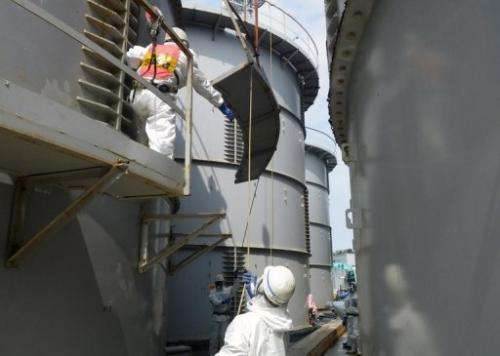Workers prepare to take apart a water tank at the Fukushima Dai-ichi nuclear plant in Japan, on September 13, 2013