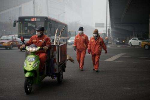 Workers wearing facemasks cross a road during heavily polluted weather in Beijing on January 29, 2013