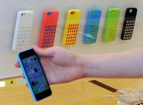 A customer checks a new iPhone 5c in front of a display of cases inside an Apple store in Hong Kong on September 20, 2013