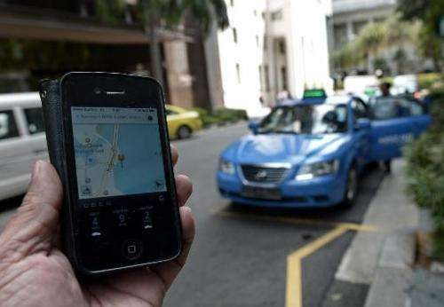 A man shows the Uber app on a smartphone on October 10, 2014