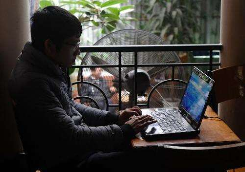 A man uses a laptop at a coffee shop in downtown Hanoi on November 28, 2013