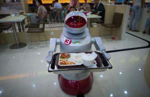 A robot carries food to customers in a restaurant in Kunshan on August 13, 2014