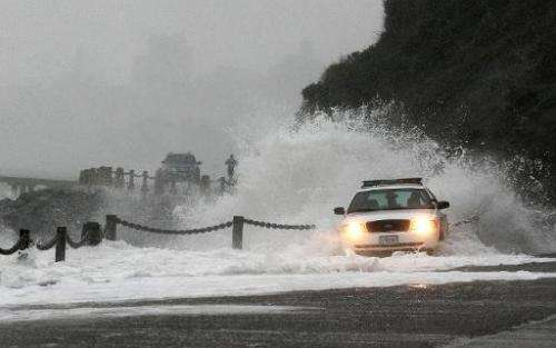 A wave crashes over a US Park Police patrol car on January 20, 2010, at Fort Point in San Francisco, California