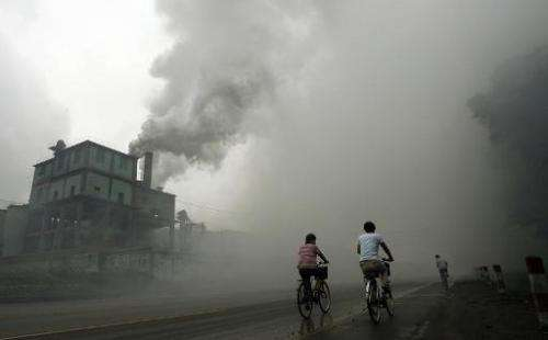 Cyclists pass through thick pollution from a factory in Yutian, China on July 18, 2006