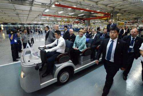 German Chancellor Angela Merkel (C) and her delegation ride an electric vehicle during a visit to the FAW-Volkswagen plant in Ch