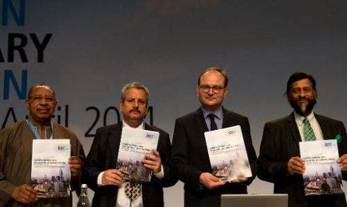 """Intergovernmental Panel on Climate Change (IPCC)pose with a copy of the IPCC report """"Climate Change 2014, Mitigation of Cli"""