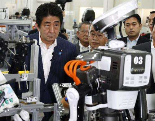 Japanese Prime Minister Shinzo Abe inspects a robot working at an assembly line of cash dispensers at a factory in Kazo, suburba