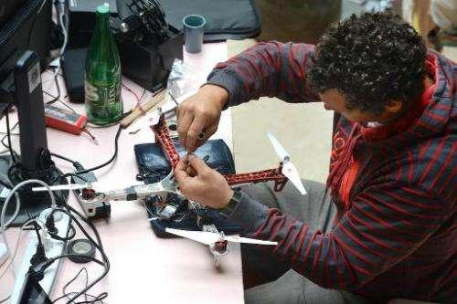 Snowboarder Xavier de le Rue adjusts a drone prototype on July 2, 2014 in France