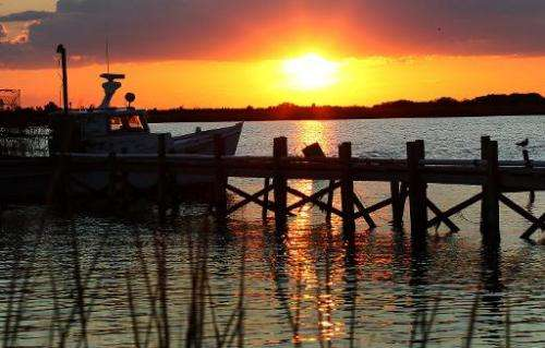 The sun sets behind a fishing boat on August 22, 2011 in Maryland