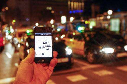 The Uber app is seen on a smartphone as taxis drive on the Paseo de Gracia in Barcelona, Spain, on December 9, 2014