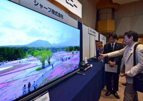 Visitors look at Sharp's 4K television and 4K capable tuner at the launch of 4K high-definition technology in Tokyo on June 2, 2