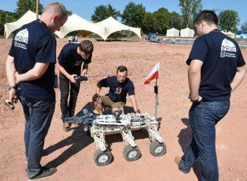"Members of the Kielce University of Technology team watch their ""Impuls"" Mars rover before the European Rover Challeng"