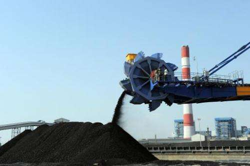 File photo taken in February 2011 shows workers using heavy machinery to sift through coal at the Adani Group's thermal power pl