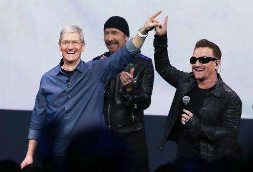 Apple CEO Tim Cook (L) greets the crowd with U2 singer Bono (R) during an Apple special event at the Flint Center for the Perfor