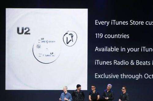 Apple CEO Tim Cook (L) announces the free download of the new U2 album on iTunes as members of U2 look on in Cupertino, Californ