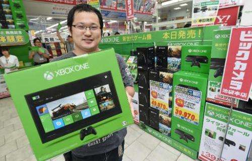 A customer holds a box containing Microsoft video game console Xbox One, at a household appliance shop in Tokyo, on September 4,