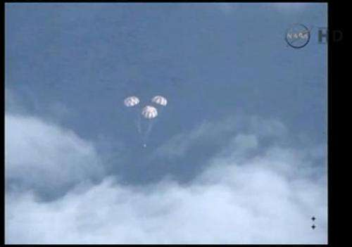 This image taken from a NASA video, shows the Orion spacecraft and its the parachutes as it descends to the Pacific Ocean on Dec