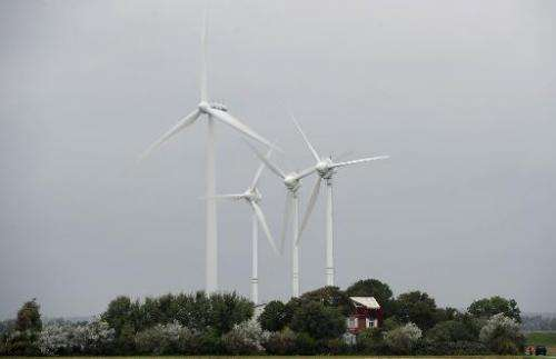 Wind turbines stand next to a house near Husum, northern Germany on September 20, 2010