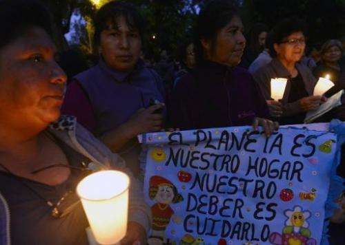 People attend a candlelight vigil organized by the Interfaith Council of Peru at a park in Lima, on November 30, 2014, before th