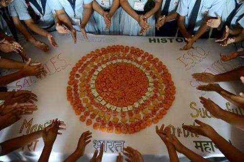 Schoolchildren in Ahmedabad mark the success of India's Mars Orbiter Mission by creating a planet Mars using orange-coloured swe