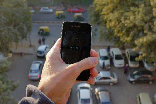The Uber smartphone app, used to book taxis using its service, is pictured over a parking lot in the Indian capital New Delhi on
