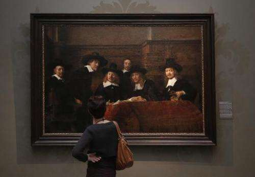 """A visitor looks at a work by Dutch artist Rembrandt Harmensz van Rijn entitled """"The Syndics of the Amsterdam drapers' Guild"""