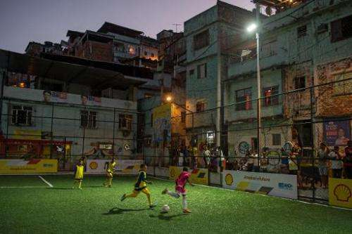 Children play football after the inauguration of the new technology pitch at Mineira favela in Rio de Janeiro, on September 10,