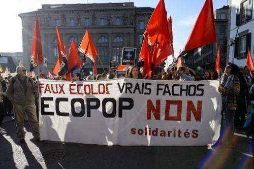 """Demonstrators hold a banner reading in French """"Fake ecologists, real fascists, No to ECOPOP"""" during a demonstration in"""