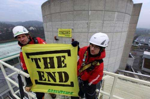 "This handout picture released by environmental organisation Greenpeace shows activists holding a banner reading ""The end&qu"