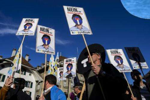 """Protesters hold placards reading in German """"No to Ecopop-dead end"""" during a demonstration in Bern against an immigrati"""