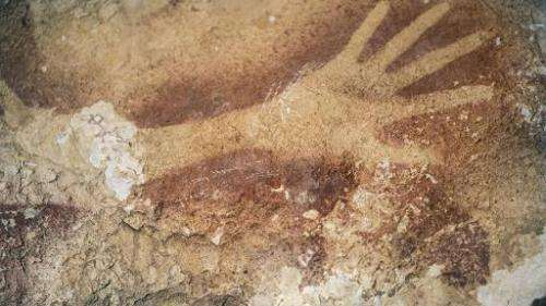 Researchers believe this silhouette of a hand on a cave wall in Indonesia is 40,000 years old. The picture was released by the j