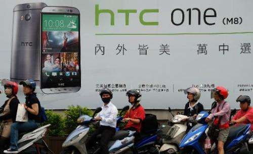 A billboard shows the latest HTC M8 smartphone in Taipei on June 6, 2014