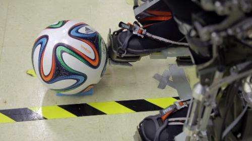 A 'Brazuca' football is seen next to an exoskeleton at Brazilian scientist Miguel Nicolelis' lab in Sao Paulo, Brazil, on Januar