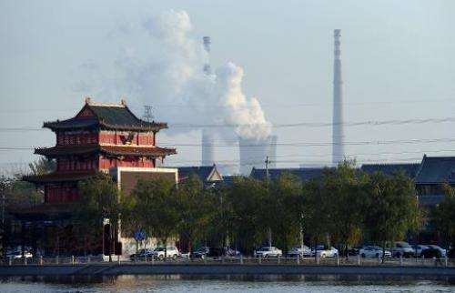 A building newly built in the architecture of imperial China stands near the cooling towers and smokestack chimneys of a coal-fi