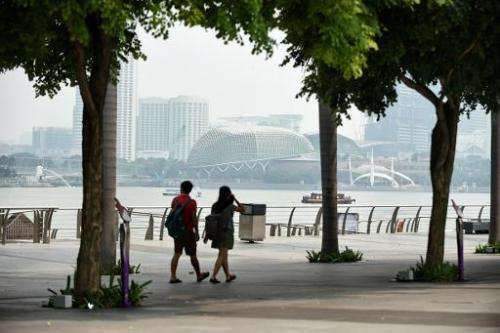 A couple walks along the promenade as haze can be seen blanketing Esplanade theatre in Singapore on September 15, 2014