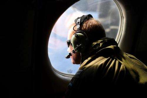 A crew member looks out an observation window aboard a Royal New Zealand Air Force (RNZAF) P3 Orion maritime search aircraft as