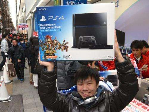 A customer reacts after buying Sony's PlayStation 4 video game console in Tokyo on February 22, 2014