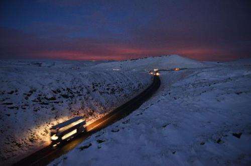 A double-decker bus travels over Standedge between snow-covered fields at dusk near the village of Diggle, northern England, on