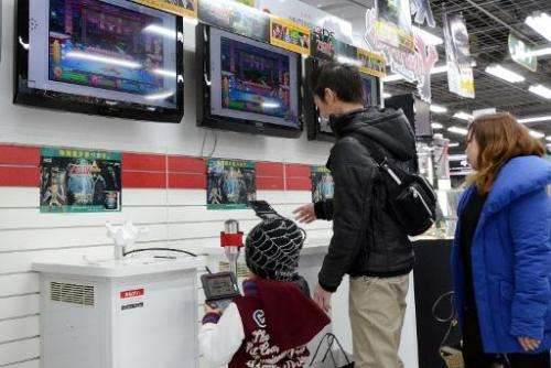 A family plays on a Nintendo portable video game console at an electronics shop in Tokyo on January 17, 2014