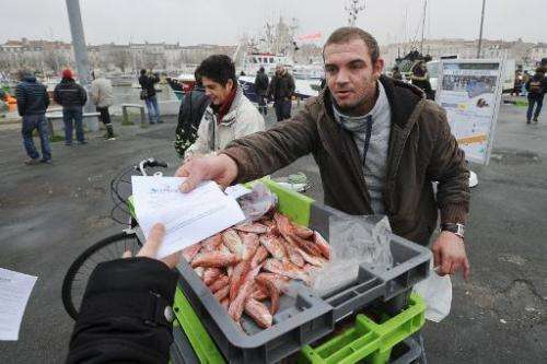 A fisherman distributes flyers during a protest against European Union fishing quotas on December 2, 2014, at La Rochelle harbor