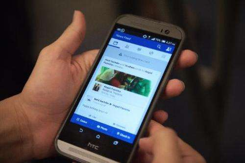 "A man check his Facebook account on his smart phone with a message reading, ""error loading news feed"" in Bangkok on Ma"