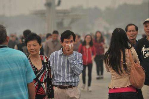 A man covers his face as he walks on a street in Beijing amid heavy smog on October 9, 2014
