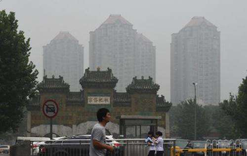 A man crosses a road on a polluted day in Beijing on July 3, 21014
