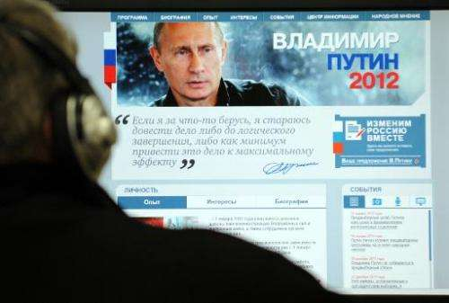 A man looks at a computer monitor displaying the main page of Russian Prime Minister Vladimir Putin's election campaign website,