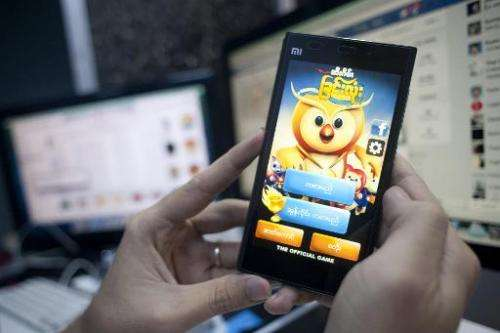 """A man plays """"Chin lone game"""" on his mobile in Yangon on September 27, 2014. New online applications are putting a loca"""
