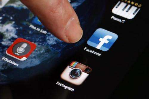 A man shows the smartphone photo sharing application Instagram on an iPhone on April 10, 2012 in Paris