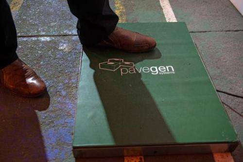 "A man steps on a ""Pavegen"" panel, invented by British Laurence Kemball-Cook, during the inauguration of a new football"